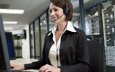 Woman wearing headset, looking at monitors in data center
